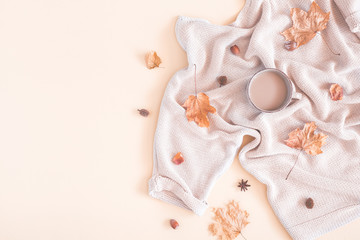 Autumn cozy composition. Cup of coffee, women fashion sweater, dried leaves on pastel beige background. Autumn, fall concept. Flat lay, top view, copy space
