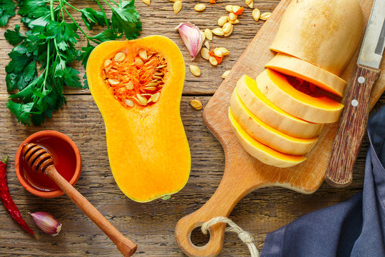 Raw organic butternut squash with ingredients for cooking on a wooden table. Selective focus