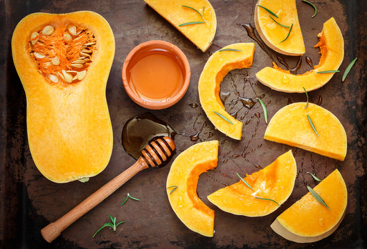Sliced raw organic butternut squash on a baking pan with honey and rosemary