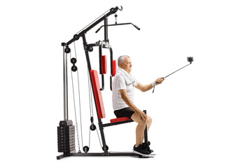 Mature man sitting on a multifunctional exercise machine and taking a selfie with a stick