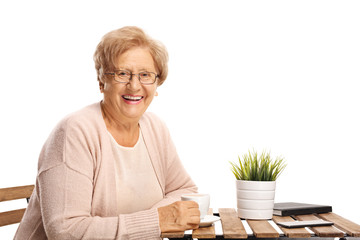 Elderly woman sitting at a coffee table and smiling