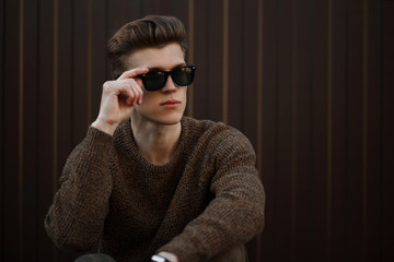 Handsome young hipster man in fashion sunglasses on the street