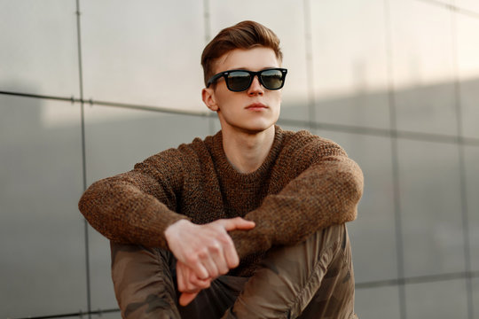 Fashion portrait of a handsome young man with sunglasses in a stylish sweater and military pants on the street
