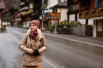 Beautiful girl photographer taking photos in the Swiss mountains. Switzerland.