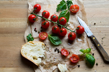 Red Food cherry tomatoes, slice of bread, basilic and a knife on brown paper wooden chopping board, rustic image
