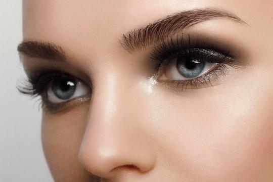Macro shot of woman's beautiful eye with extremely long eyelashes. Sexy view, sensual look. Female eye with long eyelashes
