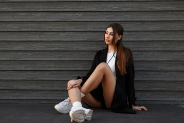 Beautiful sexy model woman in black coat with fashionable shoes sitting near a wooden wall