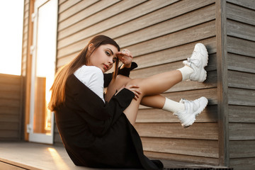 Beautiful young fashionable model woman in black stylish coat with sneakers sitting near a wooden wall at sunset