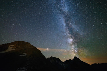 Astro night sky, Milky way galaxy stars over the Alps, Mars and Jupiter planet, snowcapped mountain range