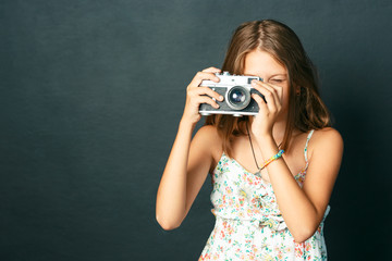 beautiful smiling child (girl) with white teeth holding a instant camera