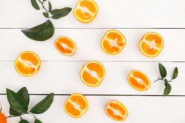 Halves of fresh delicious orange with leaves on a white wooden table