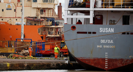 Dock workers stand on a quayside at Associated British Ports Goole facility in Goole