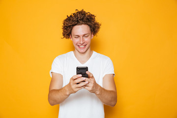 Brunette curly man in casual white t-shirt holding and using mobile phone, isolated over yellow background