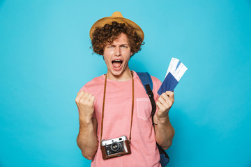 Image of photographer man 18-20 with curly hair wearing backpack and straw hat holding passport and tickets, isolated over blue background