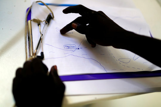 A migrant looks at the location of the port of Algeciras on a handmade map by Open Arms crew on board NGO Proactiva Open Arms rescue boat in central Mediterranean Sea