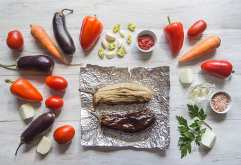 Eggplant baked on foil and vegetables are laid out on a wooden table. Vegetables on a light wooden background.