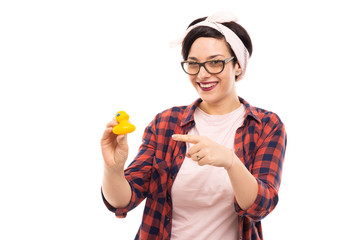 Young pretty pin-up girl pointing finger bath duck.