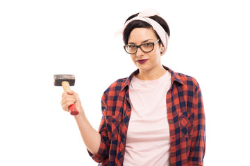 Young pretty pin-up girl holding hammer.