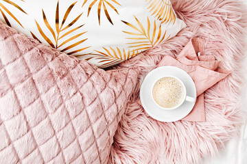 Bedding with a stylish pink pillows and cup of coffee. Copy space. Flat lay, top view Fotoväggar