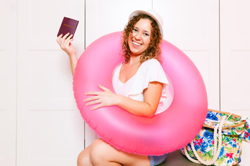 Woman sitting on luggage and holding a passport with inflatable round and ready for vacation trip. Preparing for the vacation concept