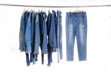 Row of Blue embroidered floral jeans ,jacket,vest on hanger