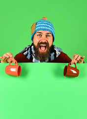 Man in warm hat holds brown cups on green background