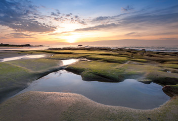 sunset seascape with beautiful rocks formation covered by green moss. soft focus due to long expose. s
