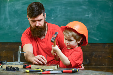 Boy, child busy in protective helmet learning to use hammer with dad. Little assistant concept. Father with beard teaching little son to use tools, hammering, chalkboard on background.