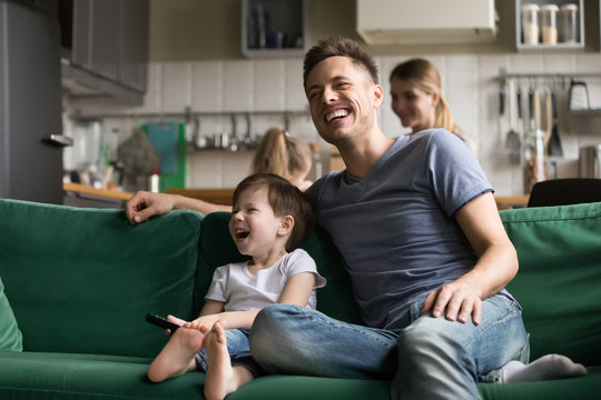 Happy dad and kid son holding remote control laughing at funny humor comedy film or tv show sitting on sofa at home, smiling father having fun with child boy watching television together on weekend