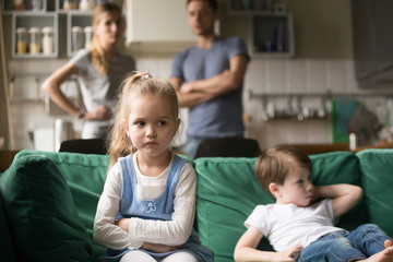 Frustrated kid girl feels upset, offended or bored ignoring avoiding worried parents and brother, little sad sister not talking to child boy after fight sulking sitting on couch, siblings rivalry