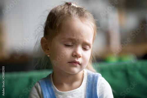 Headshot of upset little girl feeling pain, sad, tired or