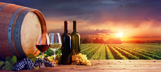 Photo sur Toile Vignoble Bottles And Wineglasses With Grapes And Barrel In Rural Scene