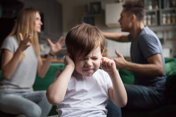 Frustrated kid son puts fingers in ears not listening to noisy parents arguing, stressed preschool boy suffering from mom and dad fighting shouting, family conflicts negative impact on child concept