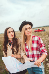 young girlfriends with map standing in field and trying to navigate