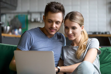 Millennial happy couple shopping together, reading internet news or relaxing on sofa with laptop, young man and woman watching interesting video or studying online using computer at home on weekend