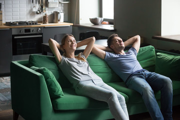 Young man and woman enjoying relaxation taking break for rest at home on comfortable couch, happy couple breathing fresh air meditating leaning on new sofa together, stress free lazy weekend concept Wall mural