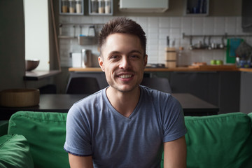 Smiling young man looking at camera sitting on sofa in the kitchen, millennial guy talking making video call, friendly vlogger speaking shooting videoblog at home, lifestyle vlog concept, headshot
