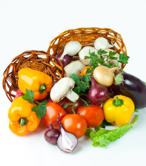 mushrooms and a variety of fresh vegetables in a wicker basket.i