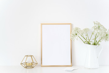 Gold frame mock up with a wild host in jug and candle. Mockup for headline design.Template for lifestyle bloggers,media