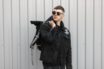 Fashionable young stylish man model with a hairstyle in black denim clothes with sunglasses with a backpack near a gray metal wall