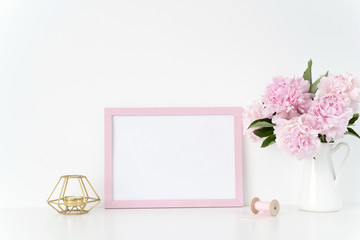 Pink landscape frame mock up with a pink peonies, candle and silk ribbons beside the frame, overlay your quote, promotion, headline, or design, great for small businesses, lifestyle bloggers and