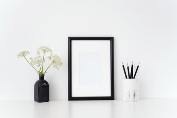 Black portrait a4 frame mock up with a summer Aegopodium podagraria in black vase and white vase with black pencils. Mockup for quote, promotion, headline, design. Template for small businesses