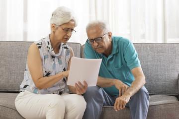 Senior couple looking at document sitting on sofa