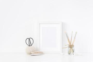 White frame mockup A5 in interior. Frame mock up background for poster or photo frame for bloggers, social media, lettering, art and design. Indoor, frame on table, lace. Summer sea mood