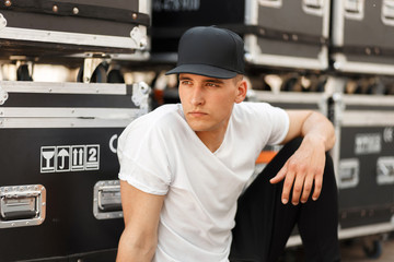 Stylish model man in a black cap and white T-shirt sitting near boxes on the street