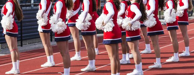 Cheerleaders cheering at a high school football game