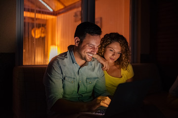Cute couple watching pictures from vacation on laptop at night.