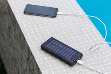 Solar smartphone charger charging phone at swimming pool
