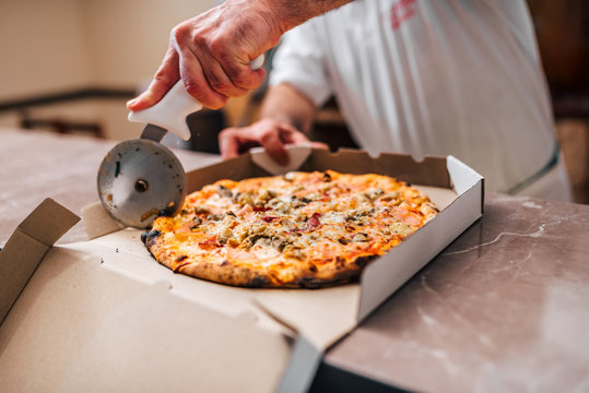 Chef cutting pizza for take away.