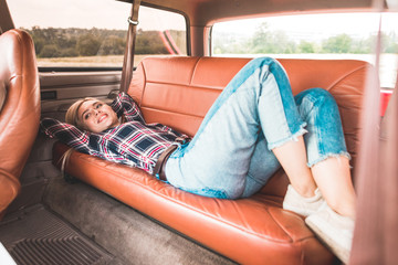 beautiful young woman lying on back seat of vintage car in field
